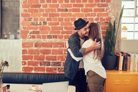 personas saludandose: Retrato de hombre joven saludo a una mujer en el café. Hombre joven que abraza a su novia en una cafetería.
