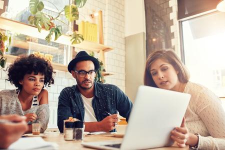 Portret van creatieve mensen zitten in een coffee shop en kijken naar laptop. Business team bespreken nieuw project ideeën in een cafe.