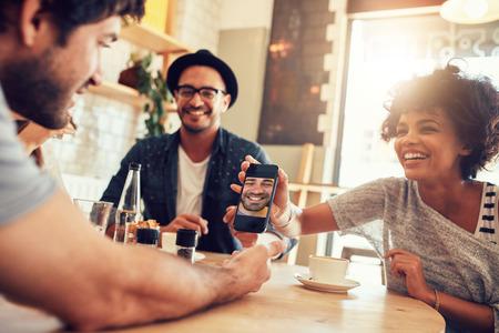 Portrét šťastné mladých přátel v kavárně a při pohledu na fotografie na chytrý telefon. Skupina smíšené rasy lidí, kteří sedí kolem stolu v kavárně a pomocí mobilního telefonu.