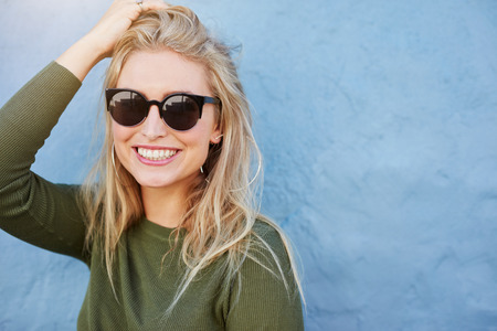 Close up shot of pretty young woman in sunglasses smiling. Attractive young female model with copy space on blue background. Stok Fotoğraf