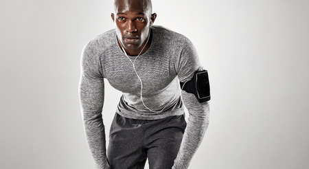 ropa deportiva: joven centrado listo para correr sobre fondo gris. Modelo masculino africano muscular en ropa deportiva. Foto de archivo