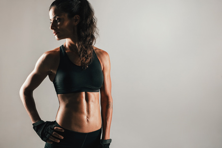 flexed: Muscular woman in shadow with gloved hand on hip and spotlight on firm abdominal muscles