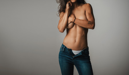 partially nude: Cropped front of partially nude woman with hands covering part of her breast while wearing open blue jeans