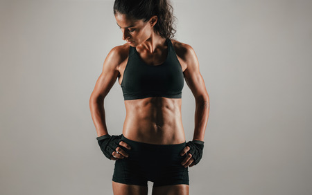 weightlifting gloves: Strong fit young woman standing with her hands on her hips showing off her muscular abs, close up cropped view on grey