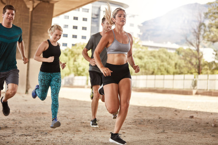 Fit young people training together outdoors. Young men and women running in the city. Stock Photo