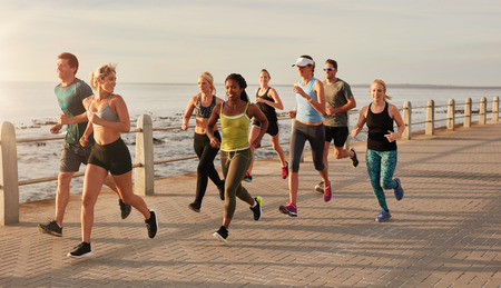 male and female: Group of runners running on urban street by the seaside. Healthy young people training together outdoors.