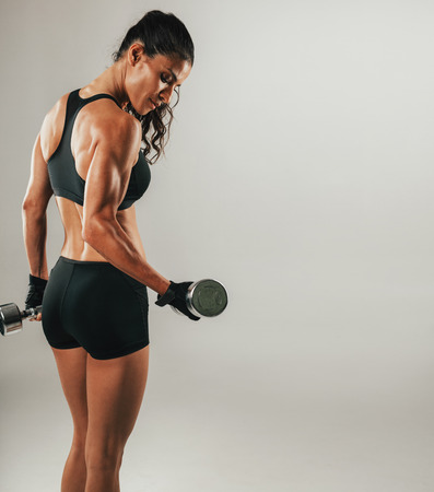 Single sweating female athlete lifting chrome dumbbell over gray background with copy space Imagens