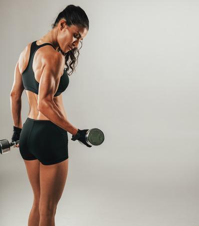 Single zweten vrouwelijke atleet opheffen chroom dumbbell over grijze achtergrond met kopie ruimte