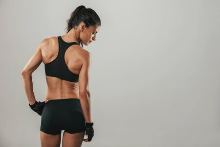 healthy looking: Healthy fit strong young woman in sportswear standing with her back to the camera looking over her shoulder, three quarter on grey with copy space