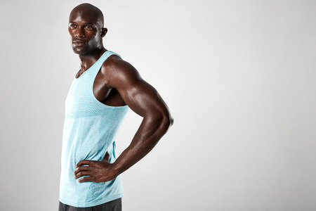 male models: Portrait of confident young african man with muscular build standing against grey background. Afro american fitness male model with hands on hips and looking away.