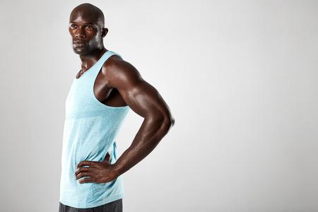 modelos hombres: Retrato de hombre joven africana seguro con la estructura muscular de pie contra el fondo gris. Modelo masculino afro americano de la aptitud con las manos en las caderas y mirando a otro lado. Foto de archivo
