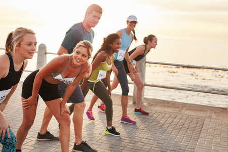 group shot: Shot of athletes at the starting point of a marathon. Diverse group of people running together on seaside promenade. Stock Photo