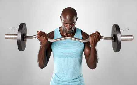 Portrait of a muscular man lifting barbell against grey background. African fitness model working out with weights.
