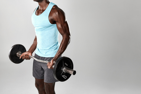 Fitness man lifting weights against grey background. African fitness model lifting barbell. Standard-Bild