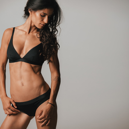 coy: Sexy young woman with a slender toned body posing in black underwear looking down with her long hair cascading over her shoulder Stock Photo