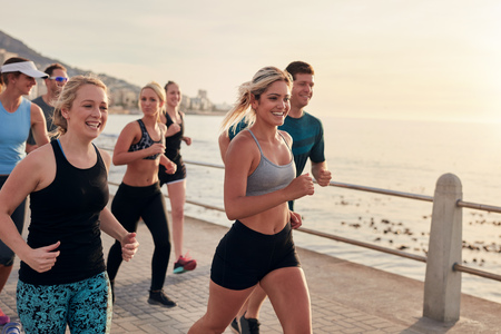 Young people running along a seaside promenade. Happy men and women runners training outdoors by the seaside. Reklamní fotografie