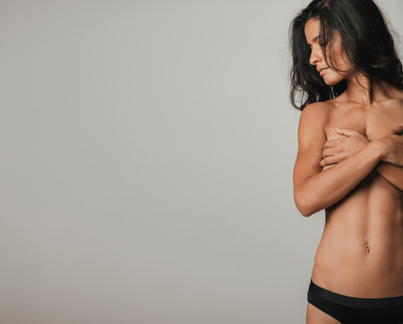 partially nude: Cropped front view of partially nude fit woman with long black hair and serious expression looking sideways while covering her chest. Copy space over gray background