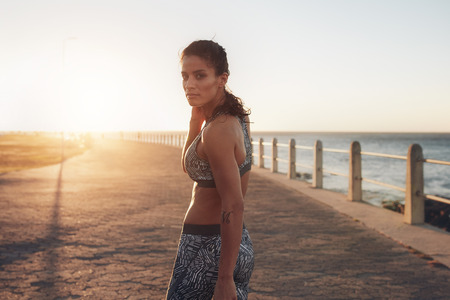 Portrait of muscular young woman in sportswear walking along a road and looking back at camera. Middle eastern female athlete on a seaside promenade at sunset. 版權商用圖片
