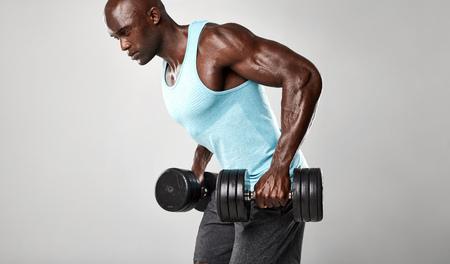 健康な若いアフリカ人はダンベル運動。灰色の背景に対して重いダンベルを持ち上げる筋肉の黒い男性モデル。