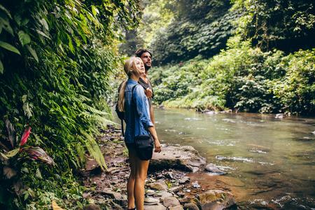 tiro al aire libre de la pareja de pie turística por un pequeño arroyo en la selva tropical. Pareja de pie caminante por secuencia de bosque.