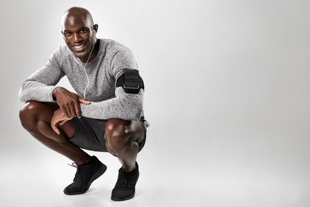 Smiling young african man with mobile phone armband and headphones crouching on grey background with copy space. Black male model listening to music.