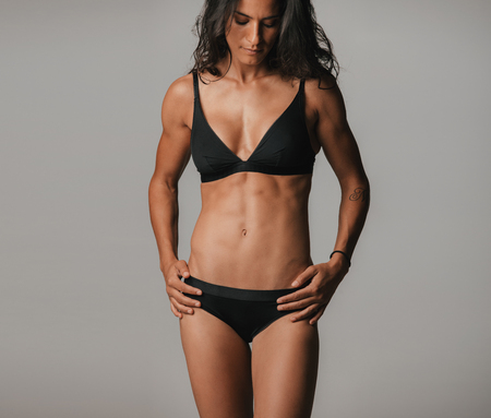 woman black background: Beautiful tanned woman stands with hands on hips while wearing black under garments