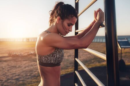 wall bars: Portrait of tired young fitness woman leaning to wall bars outdoors. Female standing by outdoor fitness equipment taking a break from her workout.