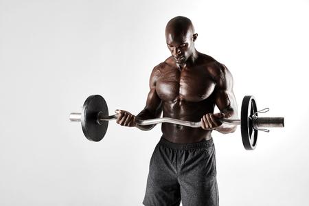 pesas: Disparo de estudio de la formación culturista joven sobre fondo gris. Muscular africano modelo masculino barra de elevación.