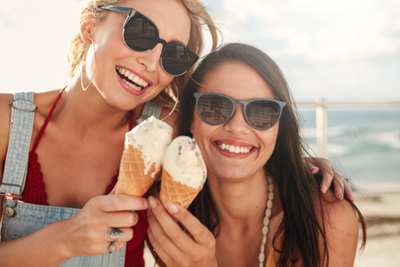 buddies: Shot of two young friends enjoying ice cream together on a summer day outdoors. Close up of cheerful female buddies eating icecream.