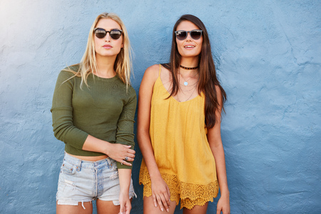 Portrait of two young women standing together against blue background. Stylish young female models posing in casuals and sunglasses.