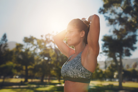 sports bar: Close up shot of fitness model doing stretching workout at the park. Determined young woman wearing sports bar exercising on a sunny day. Stock Photo