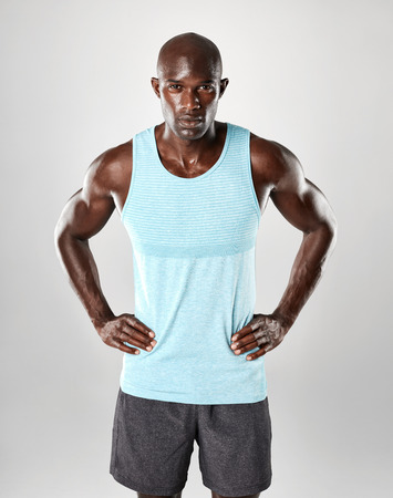 Fit and confident young muscular african man standing against grey background. Fitness male model standing with his hands on hips and looking at camera.