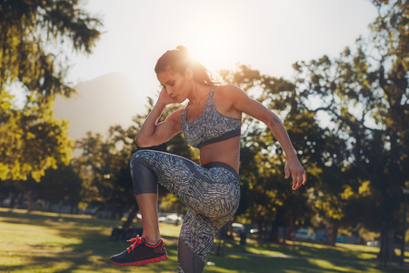 outdoor sport: Outdoor image of muscular young woman doing stretching workout at a park. Female athlete warming up before her sports training exercise.