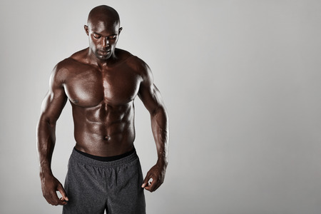 muscular build: Studio shot of muscular man posing against grey background. Shirtless male african model with muscular build.