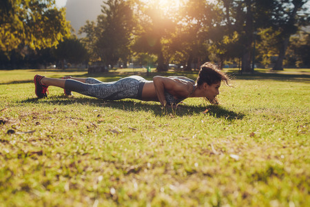 Horizontal shot of a sporty and fit young woman in sportswear working out outdoors on summer day. Sportswoman doing push ups exercise in a park.