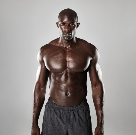 confidently: Portrait of a strong afro american man showing off his physique against grey background. Shirtless male model standing confidently.