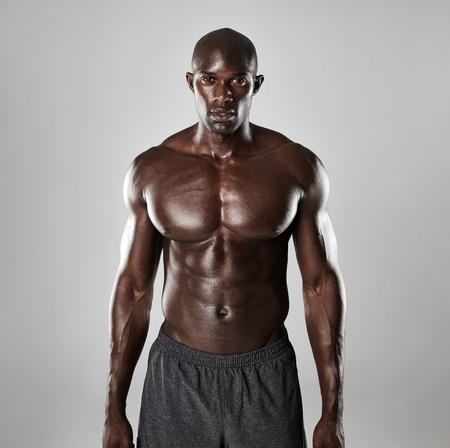 Portret van een sterke Afro-Amerikaanse man blijkt uit zijn lichaamsbouw tegen een grijze achtergrond. Shirtless mannelijk model dat zich vol vertrouwen. Stockfoto