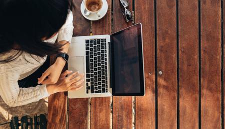젊은 여자는 그녀의 노트북 카페에서 작업의 오버 헤드보기. 인터넷 브라우징 커피 한잔과 함께 테이블에 앉아 여성의 상위 뷰 샷. 스톡 콘텐츠 - 62009692