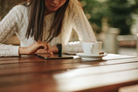 tabla de surf: Recortar foto de la mujer que usa la tableta digital mientras se está sentado en la mesa con una taza de café. Mujer navegación por Internet en el ordenador de pantalla táctil en el café.