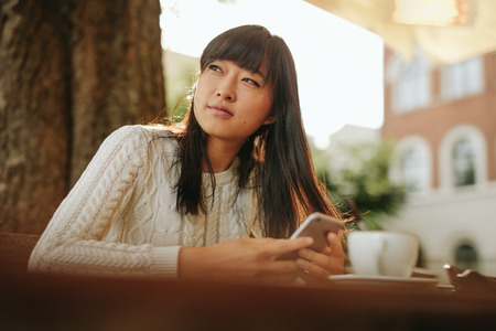 coffeeshop: Beautiful young asian woman looking away with cellphone in hand while sitting at outdoor cafe. Chinese female model relaxing at coffeeshop.
