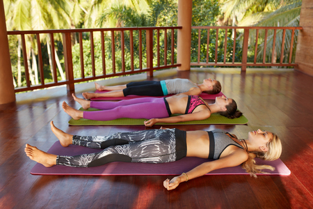 laying down: Shot of yoga class with women lying on floor. Yoga class relaxing in the Corpse pose, Savasana.