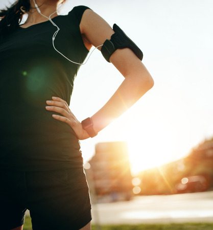 midsection: Cropped shot of fit woman standing outdoors with her hands on hips. Female runner wearing smartwatch device with sun flare, taking a break from running workout. Stock Photo