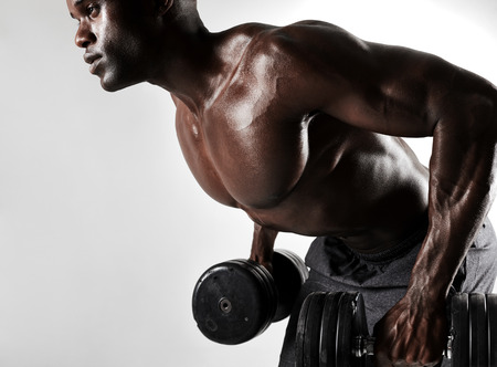 Weights: Side view close up shot of african bodybuilder exercising with dumbbells. Shirtless young man working out with heavy dumbbells on grey background. Stock Photo