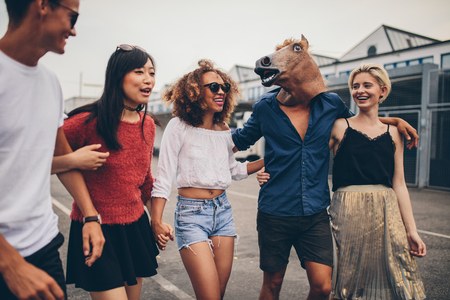 young friends: Shot of diverse group of friends having fun together outdoors. Young men and women walking outdoors, with one man wearing horse mask.
