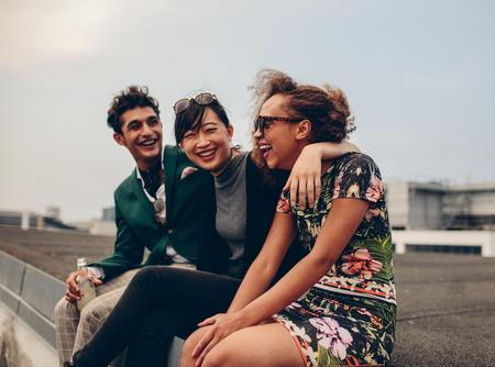 옥상에서 함께 편안 하 게 행복 한 젊은 친구의 쐈 어. 젊은 남녀 테라스에 앉아서 웃고.