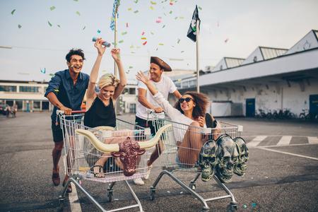 Jonge vrienden die pret op winkelwagens. Multi-etnische jongeren racen op winkelwagen.