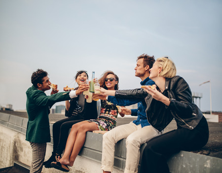Multiethnic group of young adults on terrace, drinking and celebrating. Young men and women having drinks on rooftop party.