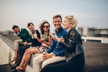 people partying: Shot of young people partying on terrace. Multiracial friends sitting together on rooftop having drinks and eating.