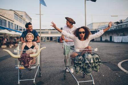 Giovani amici che hanno divertimento su un carrello della spesa. giovani multietnica corsa sul carrello della spesa.