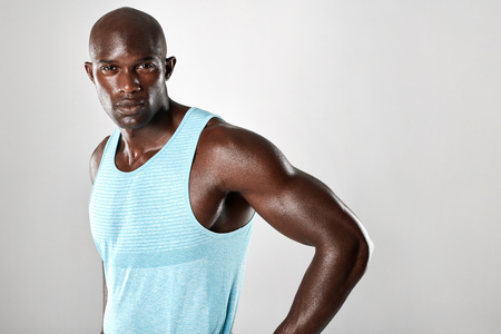 muscular build: Portrait of fit young man with muscular build standing against grey background. Afro american fitness model.